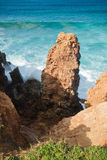 Erosion red soil cliffs rocks on atlantic coast in beautiful turquoise water Stock Photo