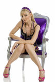 Erotic blonde. Beautiful blond sitting on a stylish chair isolated on white Stock Photos