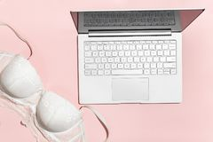 Erotic chat, virtual sex concept. White bra thrown on a modern laptop, against a pink background. Minimalistic Flat lay. Top view stock photo