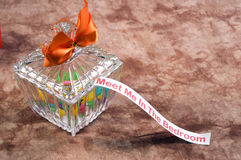 Erotic Message. An erotic message typed on paper and stuck in a glass candy dish with a bow on it royalty free stock photos