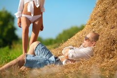 Erotic scene on hayloft. Erotic scene between brooding man lieing on hayloft and his lovely girl Royalty Free Stock Photography