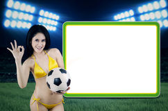 Erotic soccerfans with copyspace. Portrait of Brazil fans giving OK gesture next to copyspace. shoot at football stadion Stock Image