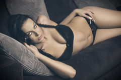Erotic woman lying on sofa Royalty Free Stock Image