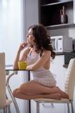 erotica Morenita bonita en delantal atractivo en cocina Foto de archivo