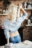 Erotico biondo della giovane donna sexy sta con la sua parte posteriore e prepara la pasta nella cucina casalinga con le borse di fotografia stock libera da diritti