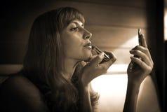 Erotisches Mädchen malt Lippen im Restaurant Stockfotos