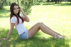 Erotisk flicka med den mini- kjolen på grönt gräs fotografering för bildbyråer