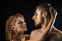 Erotiska lekar av förälskade par Sexiga par med guld- makeup för kroppkonst som isoleras på svart Guld- collagenmaskering och Arkivfoton