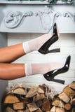 Erotyk iść na piechotę w białych czerń butach i skarpetach Młode żeńskie nogi na boże narodzenie dekorującym ściennym tle obraz royalty free