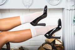 Erotyk iść na piechotę w białych czerń butach i skarpetach Młode żeńskie nogi na boże narodzenie dekorującym ściennym tle zdjęcia stock