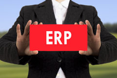 ERP Enterprise Resource Planning. Businesswoman in a black jacket shows a card with the inscription ERP Enterprise Resource Planning. Selective focus Stock Photo