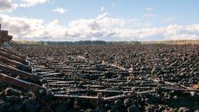 Erpice del trattore su un fondo di terreno arabile e delle nuvole freschi Fotografia Stock