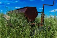 Erpice di disco d'agricoltura d'annata in un campo circondato da erba alta Immagine Stock Libera da Diritti