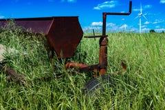 Erpice di disco d'agricoltura d'annata in un campo circondato da erba alta con i generatori eolici Immagini Stock Libere da Diritti