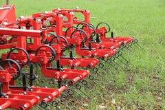 Erpice nel campo del raccolto verde dopo piovosità Immagini Stock