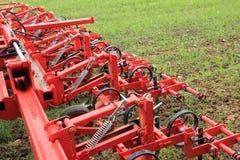 Erpice nel campo del raccolto verde dopo piovosità Immagine Stock