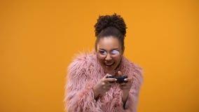 Erregbares Mädchen, das sich herzlichst ihren Sieg im Videospiel, Prüfer spielend freut stock footage