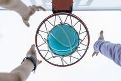 Erreichen f?r einen Basketball im Netz stockfoto