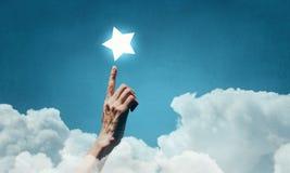 Erreichen Sie und berühren Sie den Stern Stockfoto