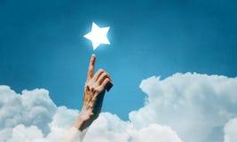 Erreichen Sie und berühren Sie den Stern Stockbild