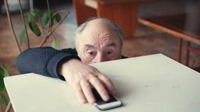 Erreichendes Telefon des alten Mannes und emotional betrachten in 4K stock video footage