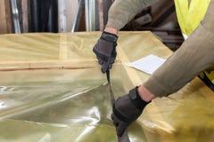 Errichten einer Wand für Rahmenhaus Arbeitskraft, die einen schützenden Film schneidet lizenzfreies stockbild