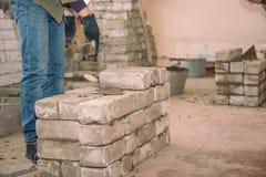 Errichten Sie eine Wand von Ziegelsteinen Studenten lernen, Ziegelsteine zu legen Zementbondziegelsteine Spachtel tamped Zement B lizenzfreie stockbilder