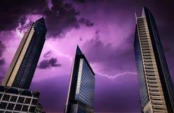 Errichtende Geschäfts-Stadt-enorme Türme und Blitz-Blitz auf Himmel Stockfotos
