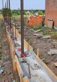 Errichtende konkrete Grundlage für neuen Zaun mit Metallunterstützungen lizenzfreie stockfotos