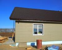 Errichtendes neues Haus mit Plastikabstellgleis-Hausmauer dach Nahaufnahme auf neuem Regen-Gossen-System, Downspout, Abflussrohr, Lizenzfreies Stockbild