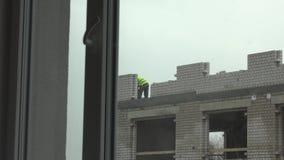 Errichtendes weißes Backsteinhaus des Berufsarbeitskrafterbauers Der Ansicht Fenster zwar stock footage