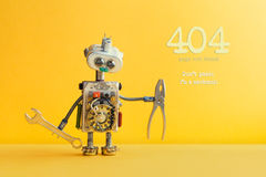 404 error page not found concept. Don`t panic I`m a mechanic. Hand wrench pliers robot handyman on yellow background. Cyborg toy lamp bulb eyes head, electric stock photography