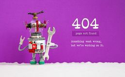 Error 404 page not found concept. Robotic humanoid handyman with hand wrench, violet background. Text message Something. Went wrong but we are working on it stock images