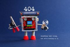 404 error web page not found. Futuristic robotic toy mechanism, light bulb and pliers in hands. Blue background. Text. Something went wrong but we are working Royalty Free Stock Images