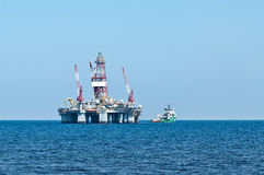 ERRV (stand-by) vessel and oil rig. Dynamically positioned emergency responce and rescue vessel making rig supply Royalty Free Stock Image