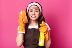 Ersch?pfte emotionale Reinigerstellung lokalisiert ?ber rosa Hintergrund im Studio, Waschlappen nahe Ohr und Reinigungsmittel hal stockfoto