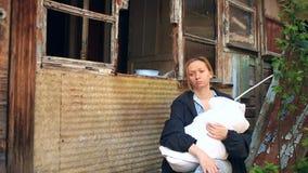Erschöpfte Frau, Mutter mit einem Kind in ihren Armen auf dem Hintergrund von bombardierten Häusern Krieg, Erdbeben, Feuer stock footage