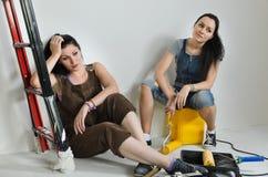 Erschöpfte Frauen, die eine Pause von der Erneuerung machen lizenzfreies stockbild