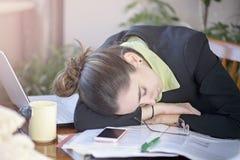 Erschöpfte Geschäftsfrau, die auf Schreibtisch im Büro schläft Stockfotografie