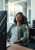 Erschöpfte Geschäftsfrau, die im Büro sich entspannt stockbild