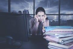 Erschöpfte Geschäftsfrau mit einem Stapel von Dokumenten Stockfotografie