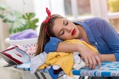 Erschöpfte junge Frau, die auf Bügelbrett schläft Lizenzfreie Stockbilder