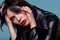 Erschöpfte junge Frau mit den roten Lippen im schwarzen Ledermantel, der ihren Kopf berührt stockfoto