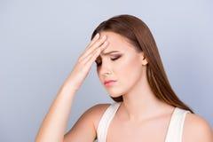 Erschöpfte junge nette Dame berührt ihre Stirn mit geschlossenem e Stockbild