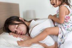 Erschöpfte müde Mutter, die morgens aufwacht stockfotografie