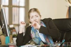Erschöpfte oder gebohrte Frau, die an ihrem Schreibtisch gähnt stockfotos