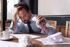 Erschöpfter deprimierter Mann, der ein Blatt Papier zerknittert Lizenzfreies Stockbild