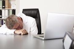 Erschöpfter Doktor, der auf seinem Schreibtisch schläft Lizenzfreies Stockfoto