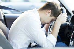 Erschöpfter Fahrer, der auf Lenkrad stillsteht Stockbilder