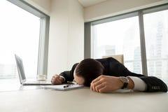 Erschöpfter Geschäftsmann, der auf seinem Schreibtisch im Büro liegt Stockfotos